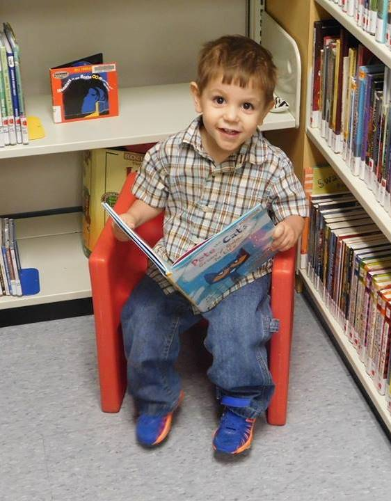 Toddler enjoys reading a book at the Lowry Branch
